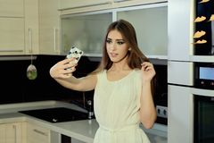 La piel blanca joven sonriente alegre femenina con el pelo moreno largo que presenta en la cocina, hace el selfie en el smartphon foto de archivo