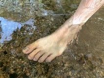 La pierna de la mujer en el agua en la cascada, relaja tiempo con la naturaleza imagenes de archivo