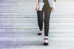 La pierna de la trabajadora del negocio camina caminando abajo de la escalera en el ou de la oficina Imagen de archivo