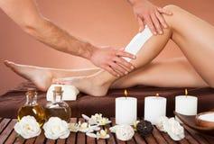 La pierna de Waxing Customer del terapeuta en el balneario de la belleza Imagenes de archivo