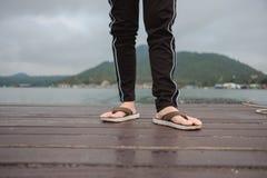 La pierna del soporte de la sandalia de la mujer que lleva solamente en el puente de madera tiene riv Fotos de archivo