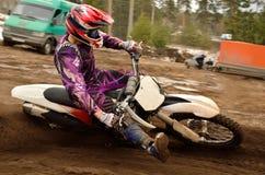 La pierna levantada motorista del motocrós adelante ejecuta el turnin imagen de archivo