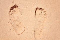 La pierna remonta en huella de la arena el pequeño resto amarillo del paraíso de la playa Fotos de archivo libres de regalías