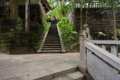 La pierre ombragée de flanc de coteau fait un pas à côté du bâtiment chinois antique Images stock