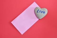 La pierre rose d'enveloppe et de coeur sur la mousse de couleur rouge embarquent Photos stock