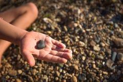 La pierre sous forme de coeur dans la paume du ` s d'enfants Photos stock