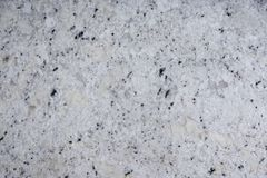 La pietra naturale del fondo di colore bianco con le macchiette scure, ha chiamato il granito bianco fantastico immagine stock libera da diritti