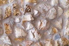 La pietra nel fondo strutturato della parete del cemento Fotografia Stock