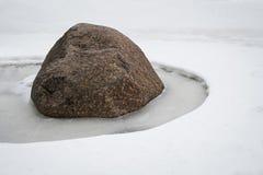 La pietra nella neve fonde la neve intorno lui Immagine Stock Libera da Diritti