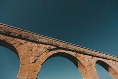 La pieza pintoresca del acueducto histórico en España contra el cielo azul imagenes de archivo