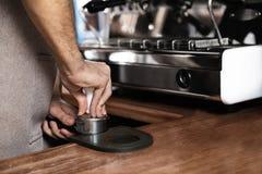 La pigiatura di barista ha macinato il caffè nel portafilter al contatore della barra, primo piano fotografia stock libera da diritti