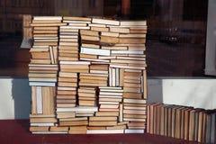 La pila caótica de libros miente en desorden en ventana de la librería, tienda del acoffee o biblioteca fotografía de archivo