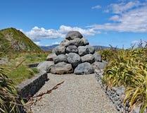 La pila de cantos rodados grises cerca de la bahía de Tarakena, isla del norte, Nueva Zelanda fue construida como un recordatorio imagen de archivo libre de regalías