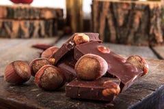 La pila de chocolate junta las piezas con las avellanas en fondo de madera Foto de archivo