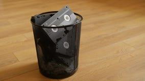 La pila de cintas video de VHS dispone en la basura sobre fondo de madera almacen de metraje de vídeo