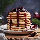 La pila de crepes americanas o los buñuelos con la fresa y el arándano atasca en la placa blanca en la Navidad adornada tabla rús foto de archivo