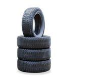 La pila de cuatro nuevos neumáticos del invierno sobre blanco Fotos de archivo