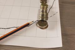 La pila de dinero acuña con el papel cuadriculado y el lápiz Fotografía de archivo