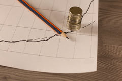 La pila de dinero acuña con el papel cuadriculado y el lápiz Foto de archivo libre de regalías