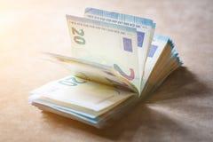 La pila de dinero digno de 20 euros miente en una superficie marrón clara de la tela en los rayos del sol Fotos de archivo libres de regalías