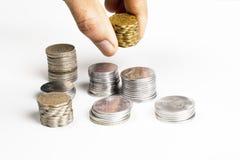 La pila de dinero en circulación indio acuña con una mano Imagenes de archivo