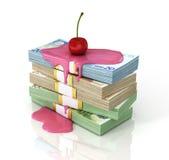La pila de dinero vertió el jarabe con una cereza en el top Foto de archivo libre de regalías