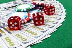 La pila de fichas de póker con los dados rueda en los billetes de dólar, dinero Tabla del póker en el casino Concepto del juego d Foto de archivo libre de regalías