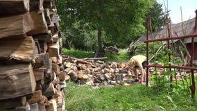 La pila de hombre tajado de madera y del granjero prepara la leña en patio trasero 4K almacen de video
