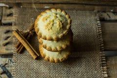 La pila de la Navidad pica las empanadas en harpillera en una caja de madera del vintage, con los palillos de canela, visión supe Imágenes de archivo libres de regalías