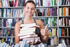 La pila de la tenencia de la muchacha de libros muestra golpe para arriba en una librería Foto de archivo libre de regalías