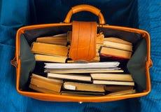 La pila de libro encuadernado reserva en una maleta vieja con Foto de archivo