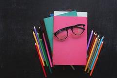 La pila de libros, efectos de escritorio de la escuela, vidrios en pizarra ennegrece el fondo De nuevo a concepto de la escuela V fotos de archivo libres de regalías