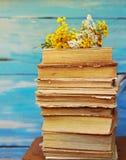 La pila de libros viejos con un ramo de amarillo florece el tansy y la milenrama Fotografía de archivo libre de regalías