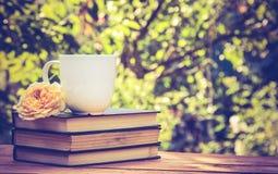 La pila de libros viejos, taza de té y subió imágenes de archivo libres de regalías