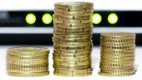 La pila de monedas de oro, como bitcoins, delante de la red se enciende fotografía de archivo libre de regalías
