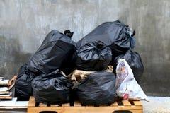 La pila de negro plástico de la basura inútil y la pila del bolso de basura pierden muchos imagen de archivo libre de regalías