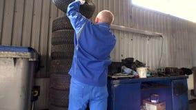 La pila de neumáticos y el mecánico toman uno Cambio estacional del neumático de coche en garaje almacen de metraje de vídeo