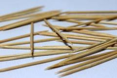 La pila de palillo de madera puso el piso blanco es un pedazo de madera acentuado corto usado para quitar pedazos de la comida fotografía de archivo libre de regalías