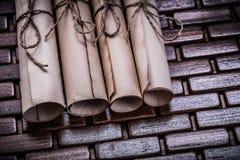 La pila de papel envejecido rueda en remar la estera de madera Imagen de archivo libre de regalías