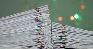La pila de papeleo tiene bokeh colorido como lapso de tiempo del fondo metrajes