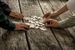 La pila de pedazos del rompecabezas que mienten en el escritorio de madera con cuatro manos alcanza Fotos de archivo libres de regalías