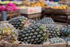 La pila de piñas orgánicas tropicales da fruto en la cesta para la venta en el mercado del granjero del tradtional de la isla de  Fotografía de archivo