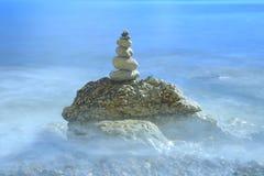 La pila de piedras rodeadas por el mar borroso agita Imagen de archivo