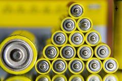 La pila de pilas AA amarillas se cierra encima de fondo coloreado extracto Fotos de archivo