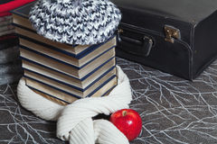 La pila de ropa del invierno y los libros con oro afilan Imagen de archivo libre de regalías