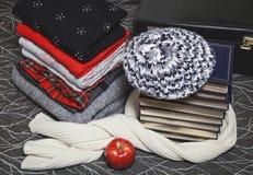 La pila de ropa del invierno y los libros con oro afilan Fotografía de archivo