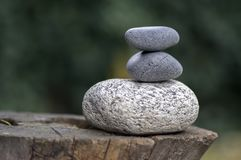 La pila de tres ZENES Stone en los guijarros de madera del tocón, blancos y grises de la meditación se eleva foto de archivo libre de regalías