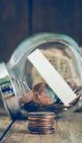 La pila de un centavo acuña en frente del tarro de cristal Imagen de archivo