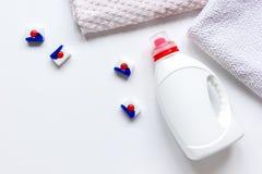 La pila degli asciugamani di bagno con il detersivo imbottiglia il modello di vista superiore della lavanderia fotografie stock