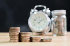La pila della moneta aumenta l'aumento risparmia i soldi con l'orologio e il ja vaghi Immagini Stock Libere da Diritti